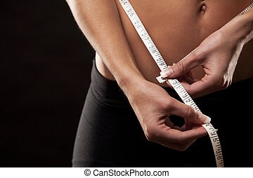 woman measuring her waist - fitness model is measuring her...