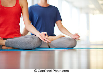 Yoga practice - Lower part of slim female and man on...