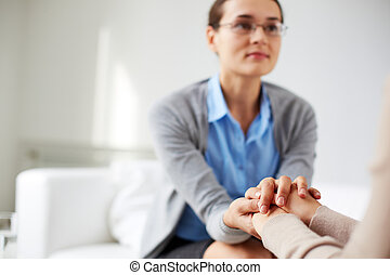 Reassuring gesture - Image of psychiatrist holding hands of...