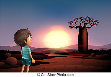 A boy at the desert watching the sunset