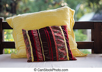 Backrest pillow - Yellow and red cushions on the sofa.