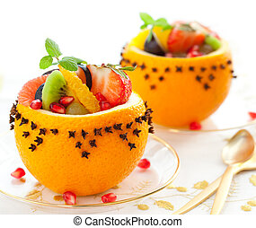 Fruit dessert - Fruit salad in hollowed-out oranges studded...