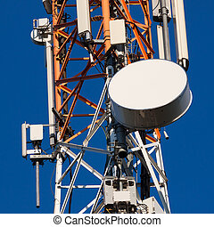 Communications tower with antennas on blue sky -...