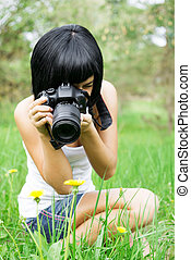 the girl photographs a dandelion - young girl taking picture...