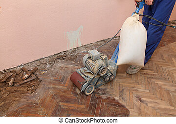 Home renovation - Worker polishing old parquet floor with...