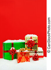 Snow covered Christmas presents red background.