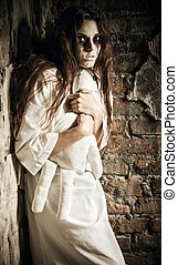 Horror scene: scared crazy girl with moppet doll in hands -...
