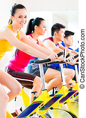 Asian people spinning bike training at fitness gym - Chinese...
