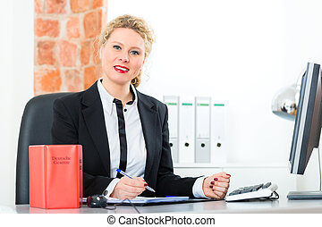 Lawyer in office with law book working on desk - Young...