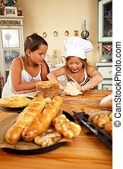 Two little girls trying to cook homemade pastry