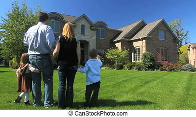 Family and House - A family stands together in their yard,...