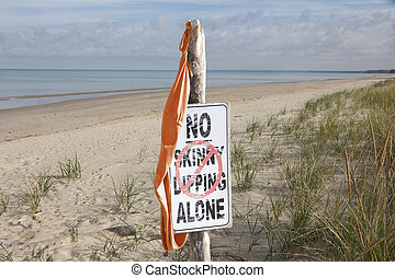Bathing Suit Hanging From Skinny Dipping Sign at Beach -...