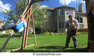 Family and Swingset - A father pushes his two kids on the...