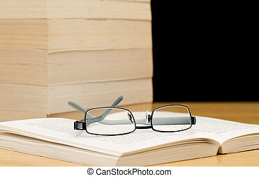 Pile of books with glasses on open book