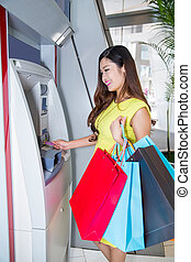young woman with credit card - young woman withdrawing money...