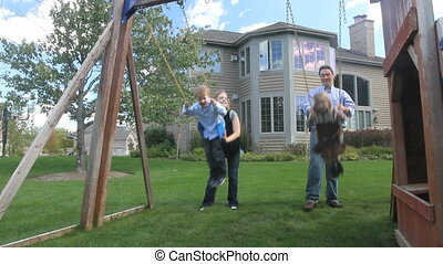 Family and Swingset 2 - A father and mother push their two...