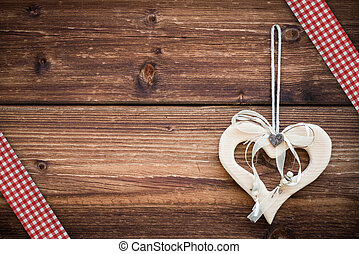 wooden heart hanging on sun burned planks with red white...