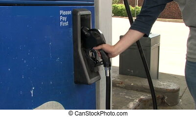 Filling Car With Gas - Panning with the gas nozzle as a man...