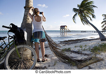 Young Woman Photographing on the Beach - A young woman takes...