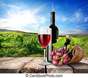 Red wine and vineyard - Red wine on the table on a...