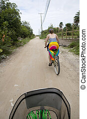 Bicycling along sandy roads - Two people bicycling along...