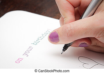 Writing birthday card - Close up of a woman's hand writing a...