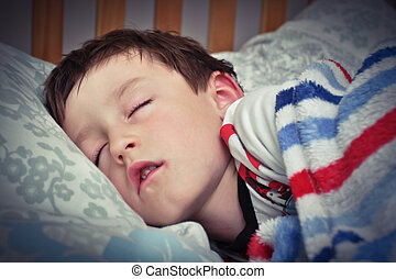 Child sleeping - A young boy asleep in bed with a blanket