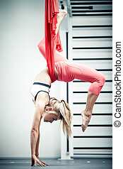 Antigravity yoga - Young woman making antigravity yoga...