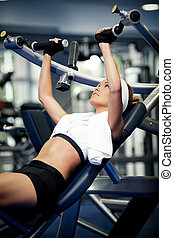Pumping up muscles - Smiling athletic woman pumping up...
