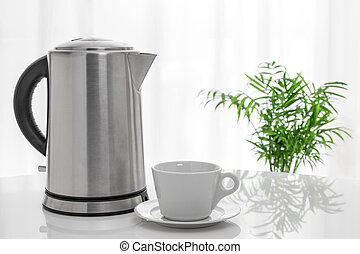 White cup and electric kettle on the table, with green plant...