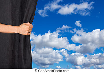 Hand opening black curtain with sky behind it
