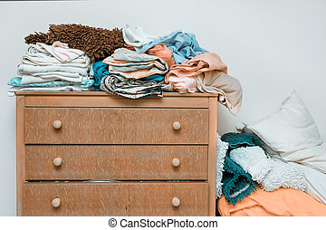 Bed linen - Piles of bed linen on a wooden chest of drawers