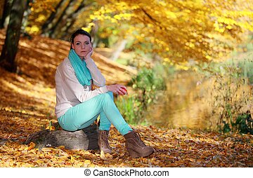 Young girl relaxing in autumnal park. Fall lifestyle concept.