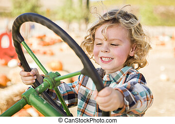 Adorable Young Boy Playing on an Old Tractor Outside -...