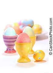 Egg cups with colored eggs on white
