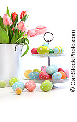 Pink tulips with colorful easter eggs on white
