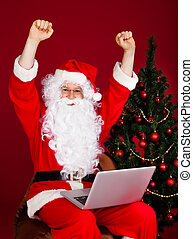 Portrait of excited santa raising his arms on red background