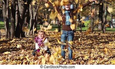 Two kids throw leaves - Two little girls throw fall leaves...