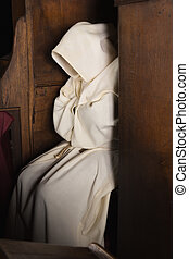 Hooded monk - Monk with hood sitting in a wooden corner of a...