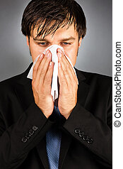 Young businessman blowing nose isolated on gray background