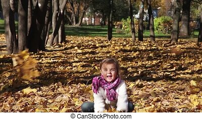 Full fun - A four years old girl throws autumn leaves and...