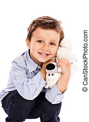 Adorable little boy holding his favourite toy on white...