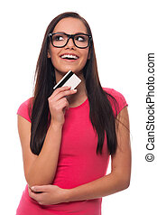 Dreaming woman planning shopping list with credit card