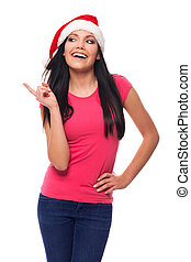 Happy woman wearing santa hat pointing at copy space