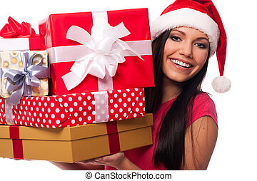 Woman wearing santa hat holding stack of christmas gifts