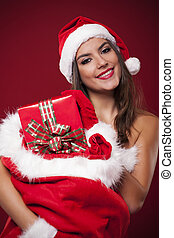 Smiling sexy woman holding sack full of christmas gifts