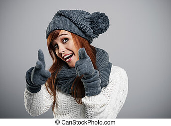Young woman wearing warm clothes pointing at camera