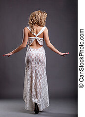 Slim girl in white negligee posing back to camera, on gray...