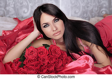 Beauty portrait. Amazing brunette woman with Red Roses lying on the bed.