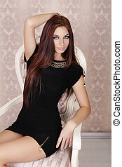 Fashion Beautiful Brunette Girl Model posing on luxury chair...